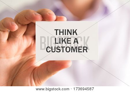 Businessman Holding A Card With Think Like A Customer Message