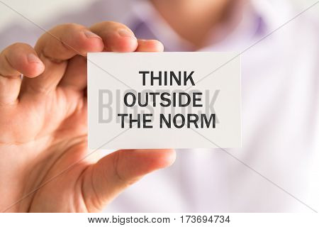 Businessman Holding A Card With Think Outside The Norm Message