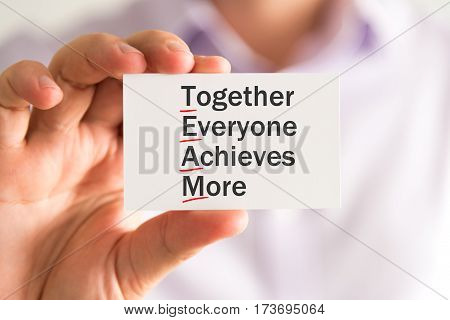 Businessman Holding A Card With Team Together Everyone Achieves More Message