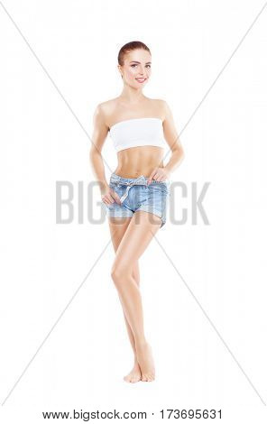 Fit, healthy and sporty woman in denim shorts isolated on white. Beautiful girl measuring her body.