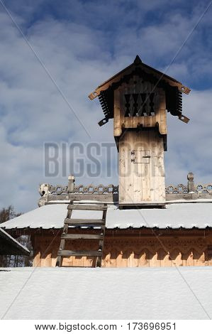 Wooden pipe and a horse decorated with carvings on the roof of the house.traditional culture of the Slavs and Russian wooden architecture, the house made of logs