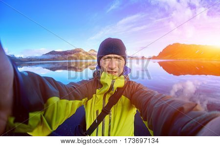man hiker photographer taking selfie on the mountain lake background in Iceland