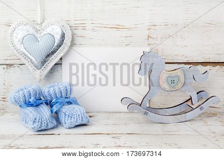 Greeting children form with blue booties and wooden horse on wooden background