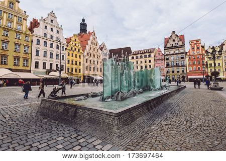 Wroclaw, Poland - September 20, 2016. Market Square fountain in Wroclaw Old Town. Tower of St Elizabeth church, traditional merchant houses, paved street and restaurants on background.
