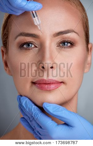 Beautiful middle age woman getting cosmetic injection in forehead