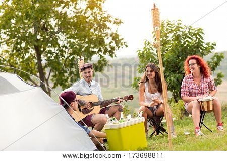 Group of youngsters camping in beautiful nature