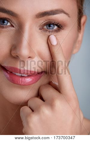 Woman holding finger on skin under eyes, checking wrinkles