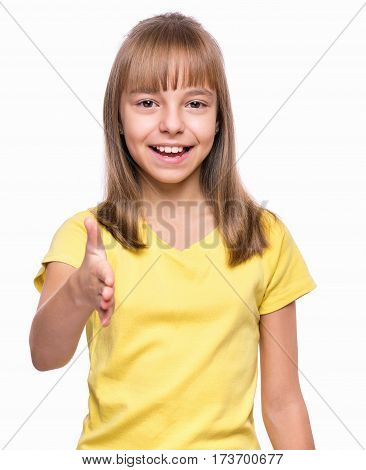 Half-length emotional portrait of caucasian girl wearing yellow t-shirt, handshake gesturing. Funny child with open hand ready for handshake, isolated on white background. Cute kid putting out his hand for shaking.