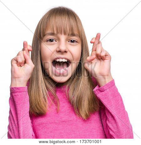 Close-up portrait of attractive caucasian hopeful girl crossing her fingers. Beautiful human face expression and emotions. Child praying or making luck gesture, isolated on white background.