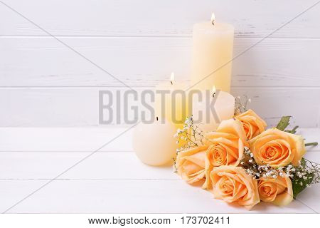 Candles and peach color roses flowers on white wooden background. Shubby chic. Place for textSelective focus.