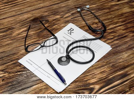 Prescription form with pen glasses and stethoscope on doctor's table.