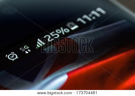 Smartphone on wooden background with 5G network sign 25 per cent charge and UK flag on the screen.