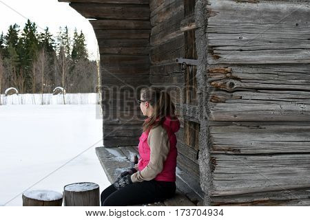 Young woman sitting outside of old log house and watching snowy field.