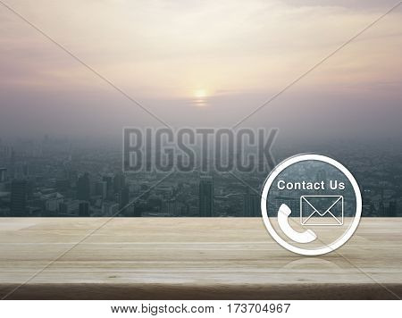 Telephone and mail icon button on wooden table over aerial view of cityscape at sunset vintage style Contact us concept