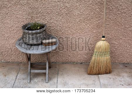 Vintage things:old French garden wooden folding table, wicker basket with flowers, old shoe brush with stiff bristles, and broom, background - yellow pink walls. Provence. France