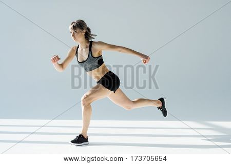 side view of running woman in sportive clothing on grey poster