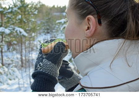 Woman eating lunch sandwich and holding coffee mug in wintry forest.