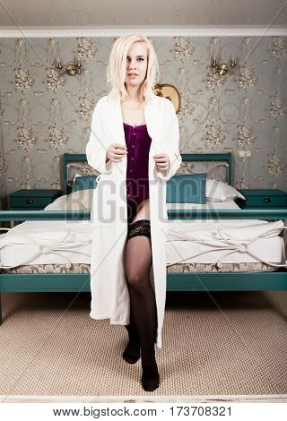 sexy beautiful blonde woman in corset, stockings and bathrobe holding fluorescent lamps sitting on a bed.