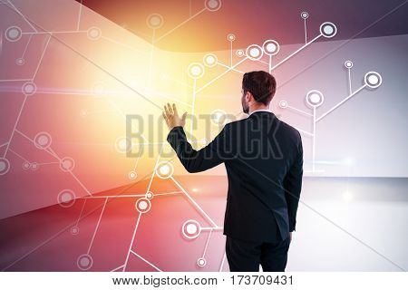 Rear view of businessman pretending to touch invisible screen against abstract room