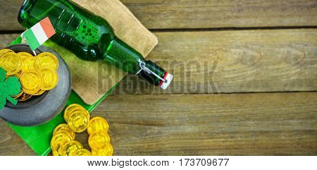 St Patricks Day shamrock with flag and beer bottle by pot filled with chocolate gold coins on wooden table