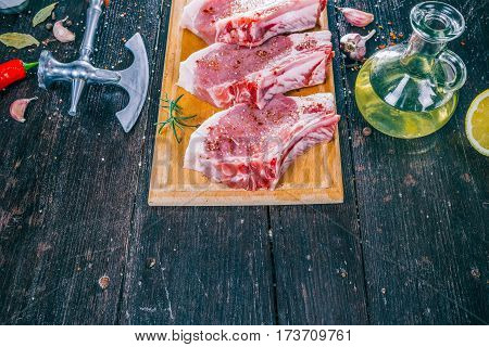 Raw porkchops with oil and spices on the dark wood