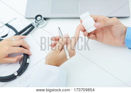 Female medicine doctor hands hold jar of pills and explain the patient how to use daily dose of pills
