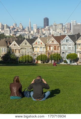 Love couple spend time in the park with Victorian Houses in San Francisco