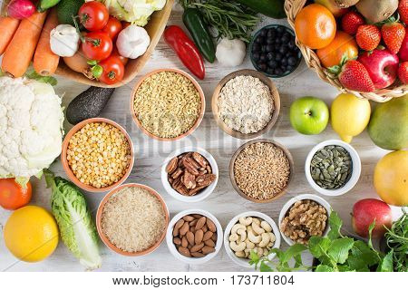 Variety of fruits and vegetables cereals nuts on the white wooden table top view selecitve focus. Basket of strawberries apples oranges kiwi bowls of oats spelt rice kamut peas; broccoli cauliflower garlic tomatoes peppers