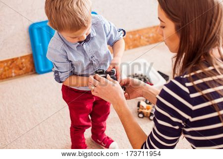 Caregiver helps the child to repair the toy car in kindergarten