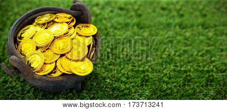 High angle shot of golden coins in bucket on field during St Patricks day