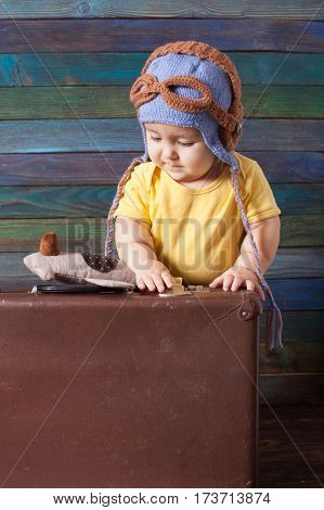 Cute baby boy in pilot hat plays with fly and suitcase