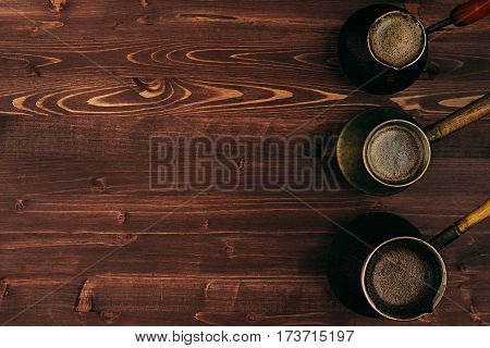 Hot coffee in shabby turkish pots cezve with tasty crema with copy space on brown old wooden board background top view. Rustic style.