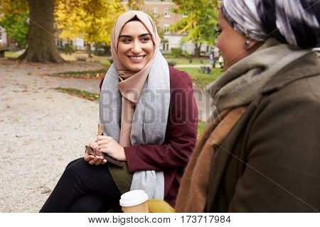 Two British Muslim Women Eating Lunch In Park Together