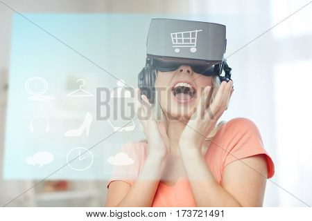 technology, augmented reality, cyberspace, e-commerce and people concept - happy amazed young woman in virtual headset or 3d glasses and headphones at home with shopping cart and menu icons projection
