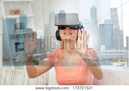 technology, augmented reality and entertainment concept - happy young woman in virtual headset 3d glasses and headphones playing game at home with singapore city skyscrapers on screen projection