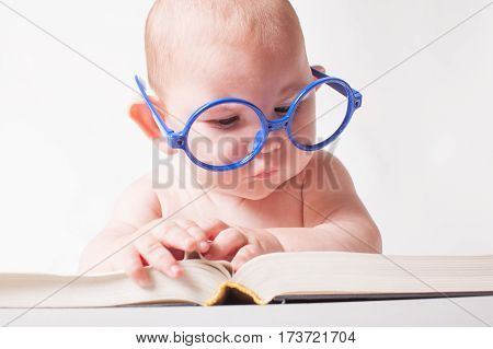 A cute baby boy reading a book in a big glasses isolated on white background