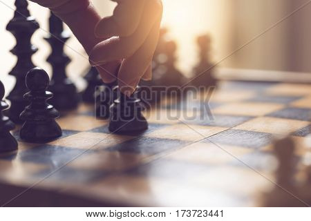 Detail of a woman's hand making the first move in a chess game moving the pawn one field forward. Selective focus
