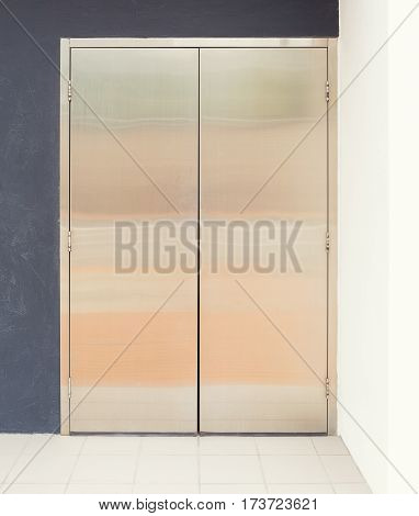 Stainless steel door and white tile floor outside office building.