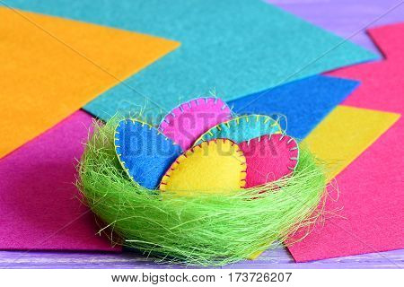 Easter eggs in a nest decoration. Handmade felt Easter eggs set in a green sisal nest isolated on colorful felt background. Crafts for decorating a house for Easter. Closeup