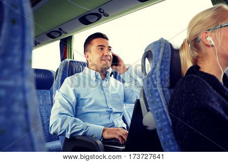 transport, tourism, business trip and people concept - smiling man with smartphone and laptop calling in travel bus