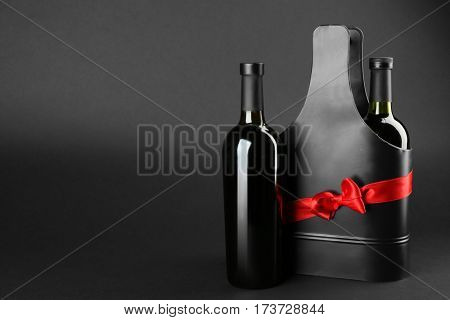 St. Valentine's Day concept. Two wine bottles and black metal gift box with satin ribbon on dark background