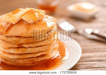 Delicious pancakes with butter and maple syrup, closeup