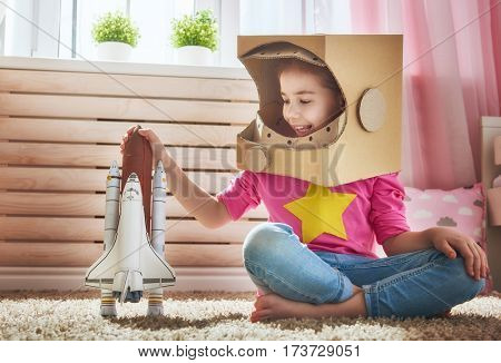 Child girl in an astronaut costume with toy rocket playing and dreaming of becoming a spacemen. Portrait of funny kid near windows.