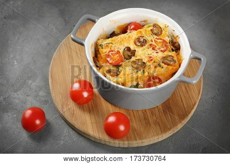 Delicious stuffed cannelloni with cherry tomatoes in ceramic pot on wooden board