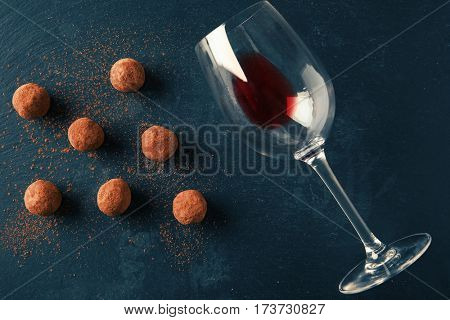 Delicious chocolate truffles and wine glass on dark background