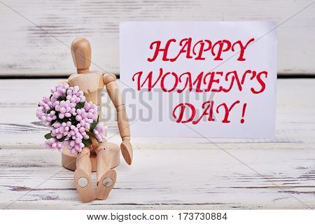 Wooden manikin, flowers and card. Wishing you special Women's day.