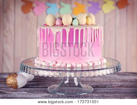 Delicious Easter cake decorated with colorful sweet eggs on stand