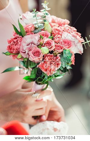 woman in a biege dress holding wedding bouquets of white and biege roses