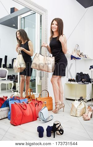 Woman trying bag and shoes sitting in a shop