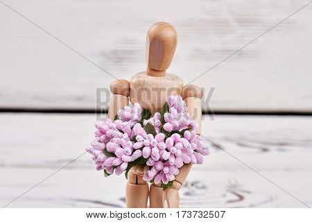 Manikin with flowers on wood. Good morning my love.